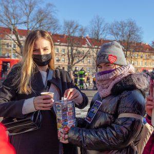 Dwie dziewczyny wkurtkach zimowych, dziewczyna poprawej stronie ma czarną maseczkę natwarzy, wlewej ręce trzyma kubek papierowy, aprawą ręką wrzuca pieniądze doskarbonki WOŚP którą trzyma dziewczynka polewej stronie.