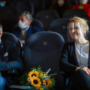 publiczność wmaseczkach ochronnych wstudiu festiwalowym podczas otwarcia, wbezpiecznej odległości siedząca nafotelach kinowych. Polewej stronie siedzi Burmistrz Słubic wczarnej maseczce, poprawej stronie siedzi uśmiechająca się kobieta wprzyłbicy ochronnej. Między nimi nasiedzeniu leży bukiet słoneczników.