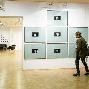 Wnętrze Galerii Okno. Kobieta wmaseczce ochronnej oglądająca jedną zprac. Składa się ona zsiedmiu zdjeć oprawionych wszare passe partout icienkie czarne ramy 100x70cm, wtle wnętrze galerii.
